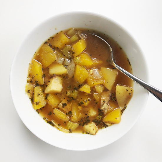 Chunky vegetable soup in a white bowl with a spoon
